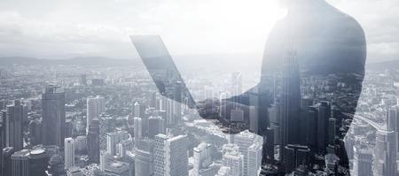 Doppelbelichtung Geschäftsmann mit schwarzem T-Shirt, Panoramablick. Banker halten moderne Notebook hands.Work Online-Banking. Isolierte weiße, moderne Wolkenkratzer Stadt Hintergrund.