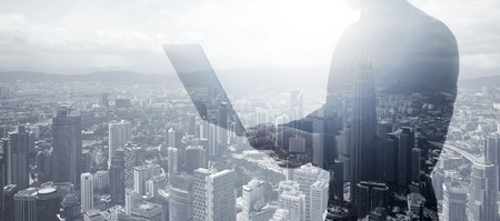 business connection: Double exposure businessman wearing black shirt, panoramic view. Banker holding contemporary notebook hands.Work online banking. Isolated white,modern skyscraper city background.
