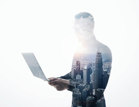 Double exposure bearded businessman wearing black suit and glasses.Banker holding contemporary notebook hands.Work online banking.Isolated white,modern skyscraper city background. Imagens