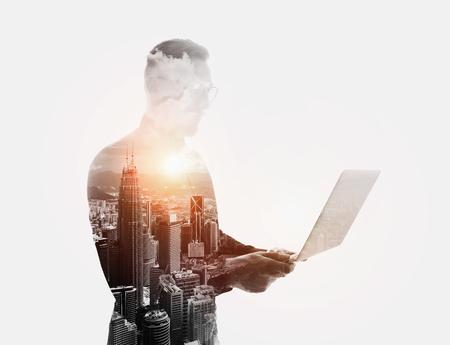 exposicion: Doble exposición con barba negocios usando la camisa negro y sosteniendo glasses.Banker hands.Work portátil contemporánea en línea banking.Isolated blanco, ciudad moderna atardecer de fondo.