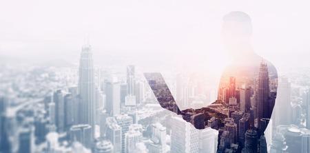 Doppelbelichtung Foto bärtiger Geschäftsmann schwarzen T-Shirt und glasses.Banker mit zeitgenössischen Notebook Händen tragen, mit online arbeiten banking.Panoramic modernen Wolkenkratzer Stadt Hintergrund Blick