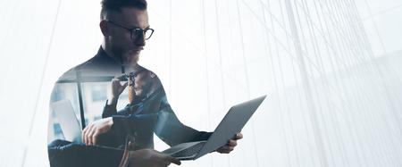 exposicion: Doble exposición barba negocios usando la camisa negro y gafas, de la mano portátiles contemporáneas. Retrato joven banquero usando la computadora portátil en la oficina moderna, rascacielos de fondo.
