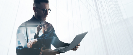 Double exposure bearded businessman wearing black shirt and glasses,holding contemporary notebook hands. Portrait young banker using laptop in modern office, skyscraper background.