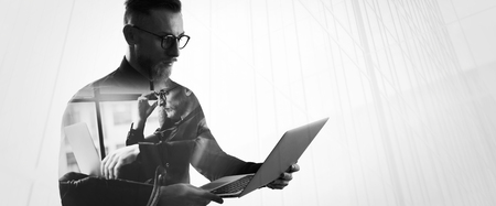 connection: Double exposure bearded businessman wearing shirt and glasses,holding contemporary notebook hands. Portrait young banker using laptop in modern office, skyscraper background.