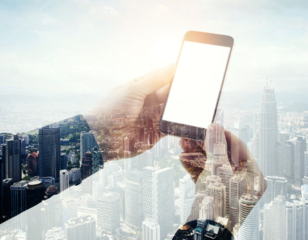 Double exposure photo businessman holding modern smartphone hands. Panoramic view contemporary city and clouds background. White blank screen ready for your business information.Horizontal