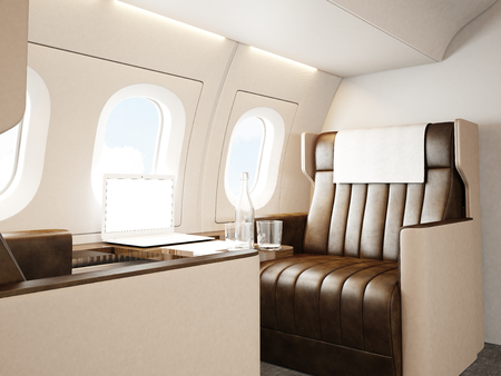 Photo interior of luxury private jet. Empty leather chair, modern generic design laptop table. Blank white screen ready for your business information. Horizontal mockup.