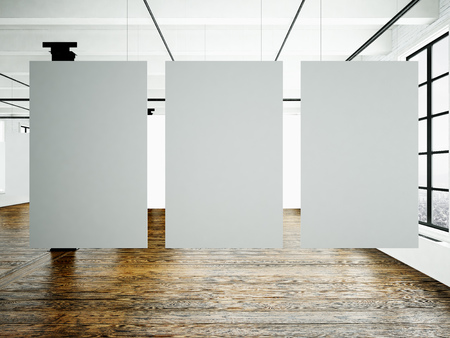 Photo of museum interior in modern building.Open space studio. Empty white canvas hanging.Wood floor, bricks wall,panoramic windows. Blank frames ready for bussiness information.Horizontal.