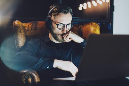 Foto barbuto imprenditore indossando occhiali di relax moderno loft office.Man seduto in poltrona d'epoca, l'ascolto di musica portatile night.Using notebook contemporanea, sfondo sfocato.