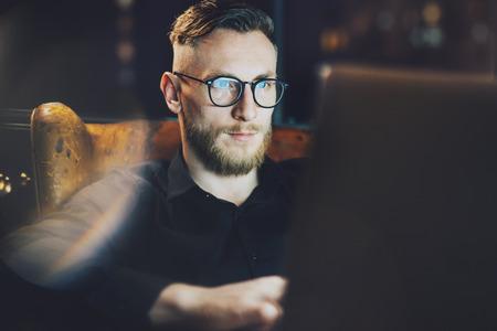 trabajando duro: Foto estilo banquero sigue trabajando en la oficina loft moderno después del día duro. Hombre sentado en la silla de la vendimia en la noche. Usando la computadora portátil contemporánea, fondo borroso. La luz suave, sombras.