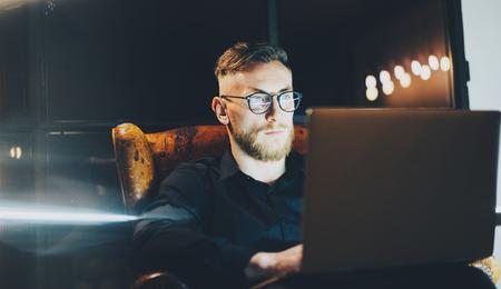 trabajando duro: Imagen banquero barba sigue trabajando en la oficina loft moderno después del día duro. Hombre sentado en la silla de la vendimia en la noche. Usando la computadora portátil contemporánea, fondo borroso. La luz suave, sombras. Foto de archivo