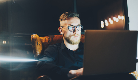 hard day at the office: Picture bearded banker still working on modern loft office after hard day. Man sitting in vintage chair at night. Using contemporary laptop, blurred background. Soft light, shadows.