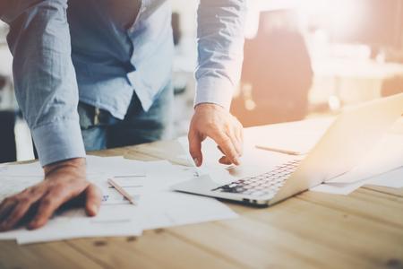 Office-Welt. Geschäftsmann auf dem Holztisch mit neuen Business-Projekt in der modernen Coworking Ort arbeiten. Man berührt Pad zeitgenössischen Laptop. Horizontal Mockup.