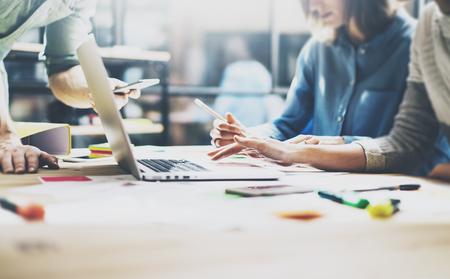Réunion de l'équipe process.Photo jeunes chefs d'entreprise équipe travaillant avec le nouveau démarrage project.Notebook sur la table en bois, en tapant keyboard.Using smartphones modernes, envoyant un message, analyser les plans.