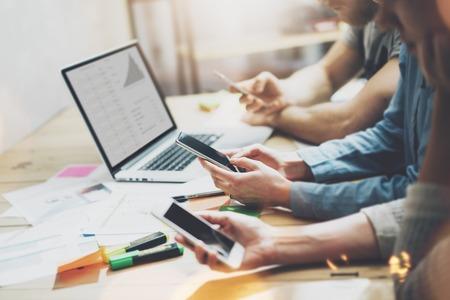 Digitale wereld. Photo jonge business managers crew werken met nieuwe startup project.Notebook op houten tafel. Met behulp van moderne smartphones, het typen bericht, analyseert plannen scherm.