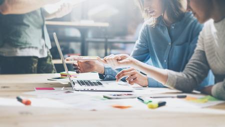 Squadra incontro process.Photo giovane manager aziendali equipaggio a lavorare con nuova startup project.Notebook su tavola di legno, digitando keyboard.Using moderni smartphone, sms messaggio, analizzare i piani.