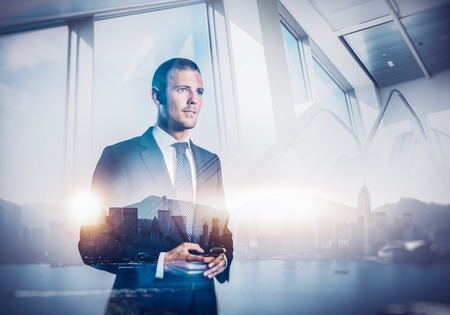 Smartphone holding in businessman hands. Double exposure of panoramic city view on the background Imagens