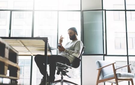 Foto barbudo hombre de trabajo con el nuevo proyecto moderno loft de espacio abierto. Usando contemprary manos de telefonía móvil. Proceso creativo. fondo de la ventana panorámica. Borrosa, efecto de película