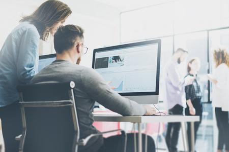 Processo di coworking, team di designer che lavorano in ufficio moderno. Giovane manager creativo di foto che mostra il nuovo monitor di idea di avvio. Desktop computer sul tavolo di legno. Sfondo sfocato, effetto pellicola.