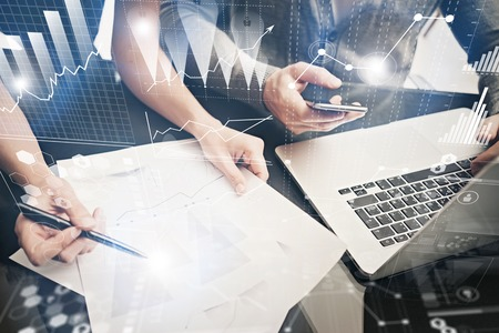 Brainstorming meeting concept.Businessmans crew working investment project modern office.Using contemporary laptop. Worldwide connection technology, stock exchanges graphics interface.
