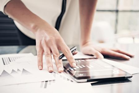 bolsa de valores: Foto mercado de lectura de la mujer informa tableta moderna y pantalla táctil con iconos de la bolsa de valores de todo el mundo. Trabajando oficina proceso. Horizontal.