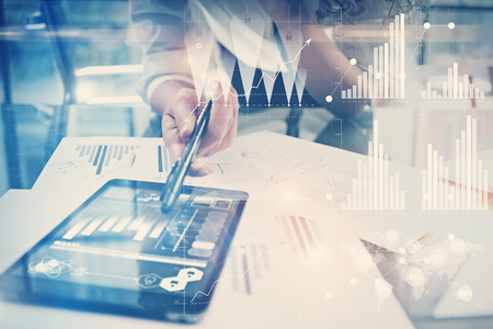 finance director: Image of working process. Finance director work new global project in worldwide bank office. Using modern tablet. Graphics icons, tax, stock exchanges interface.