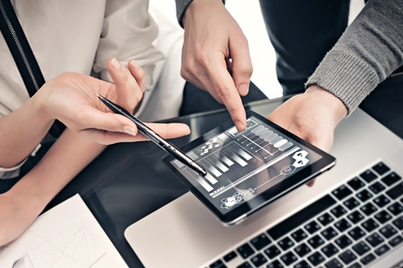 Investment department working process.Photo man showing reports modern tablet screen.Statistics graphics screen.Private banker manager holding pen for signs documents. New business project startup