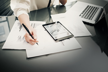 Investment manager working process.Photo woman using reports modern tablet screen.Statistics graphics screen.Private banker boss holding pen for signs documents. New business project startup