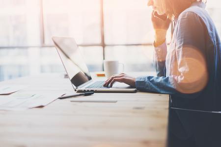作業プロセスの近代的なオフィス。アカウント マネージャーが新しいビジネスのスタートアップと木製のテーブルを操作します。タイピング現代の