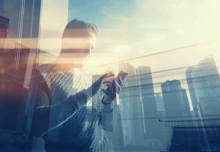 Double exposure photo man touching screen smartphone.Picture bearded trader manager in modern office panoramic view.Contemporary city skyscrapers background. Film and bokeh effect. Stock Photo