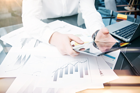 Picture man touching modern tablet screen.Trader manager working new private banking project office.Using electronic device.Graphic icons,stock exchanges reports table. Film effect