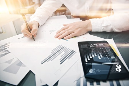 analyze: Investment manager working process.Picture trader work market report modern tablet.Using electronic device.Graphic icons,stock exchanges report screen.New business project startup.Horizontal
