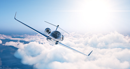 Image of black luxury generic design private jet flying in blue sky at sunset. Huge white clouds background. Business travel picture. Horizontal . Stock Photo