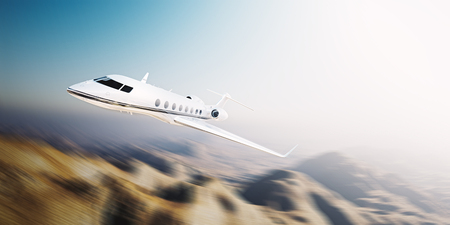 Image of white modern and luxury generic design private jet flying at sunrise over uninhabited desert.Mountains background.Business travel concept. Horizontal,motion blurred effect. Stock Photo