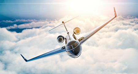 Image of black luxury generic design private jet flying in blue sky at sunset. Huge white clouds background. Business travel concept. Horizontal .