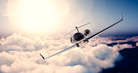 Image of black luxury generic design private jet flying in blue sky at sunset. Huge white clouds background. Business travel concept. Horizontal , front view. Stock Photo