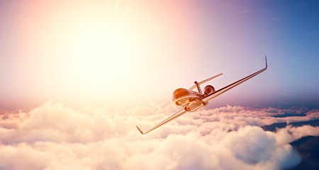 Image of black luxury generic design private jet flying in blue sky at sunset. Huge white clouds and sun background. Business travel concept. Horizontal , front view.