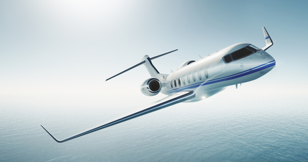 Photo of luxury generic design private jet flying over the sea. Business travel concept. Empty blue sky at the background. Horizontal .