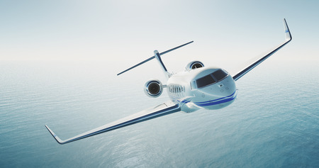 Picture of white luxury generic design private jet flying over the empty sea. Blue sky at background. Luxury travel concept. Horizontal .