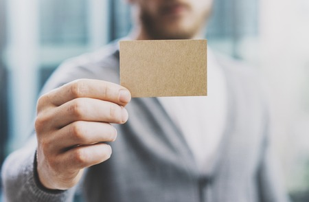 private information: Man wearing casual shirt and showing blank craft business card. Blurred background. Ready for private information. Horizontal Stock Photo