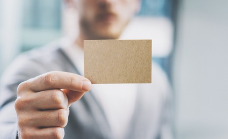 private information: Closeup photo man wearing casual shirt and showing blank craft business card. Blurred background. Ready for private information. Horizontal Stock Photo