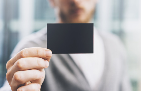 private information: Man wearing casual shirt and showing blank black business card. Blurred background. Ready for private information. Horizontal
