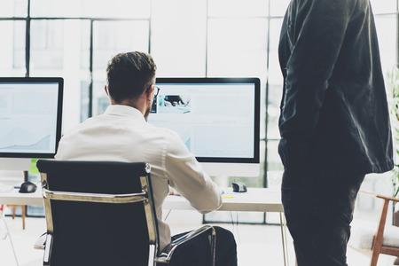 red informatica: proceso de coworking, los diseñadores del equipo de trabajo office.Photo moderna joven director creativo que muestra la nueva pantalla de inicio idea. Las computadoras de escritorio en la mesa de madera. fondo borroso, efecto de película. Foto de archivo