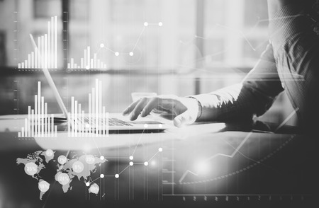 management team: Business concept photo.Manager working table with new startup project. Man using contemporary laptop. Graphics icon,worldwide stock exchanges interfaces.Horizontal. Film effect.