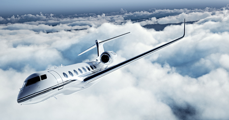 Realistic picture of White Luxury generic design private jet flying over the earth. Empty blue sky with white clouds at background. Business Travel Concept. Horizontal.