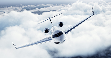 private airplane: Realistic image of White Luxury generic design private airplane flying over the earth. Empty blue sky with white clouds at background. Business Travel Concept. Horizontal.