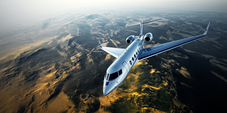 Realistic photo of silver generic design private jet flying over the mountains. Empty blue sky with sun at background. Business Travel by modern luxury aircraft. Horizontal.