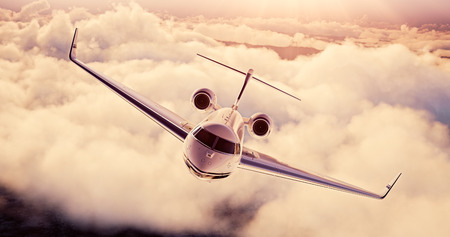 private airplane: Realistic image of White Luxury generic design private airplane flying over the earth at sunset. Empty blue sky with huge white clouds  background. Business Travel Concept. Horizontal.