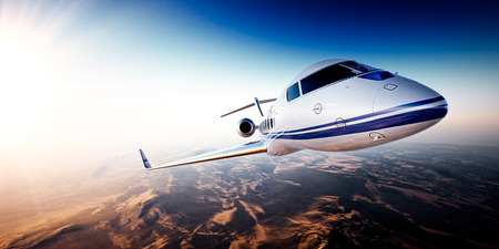 first plane: Realistic photo of white generic design private Jet flying over the mountains. Empty blue sky with sun at background.Business Travel by modern Luxury Plane.Horizontal.Closeup image. Stock Photo
