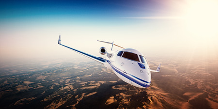 Realistic photo of white generic design private Jet flying over the mountains. Empty blue sky with sun at background.Business Travel by modern Luxury Plane.Horizontal.Closeup picture.