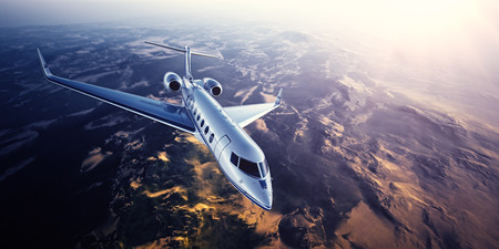 Realistic photo of silver generic design private Jet flying over the mountains. Empty blue sky with sun at background.Business Travel by modern Luxury Plane.Horizontal.Closeup photo.